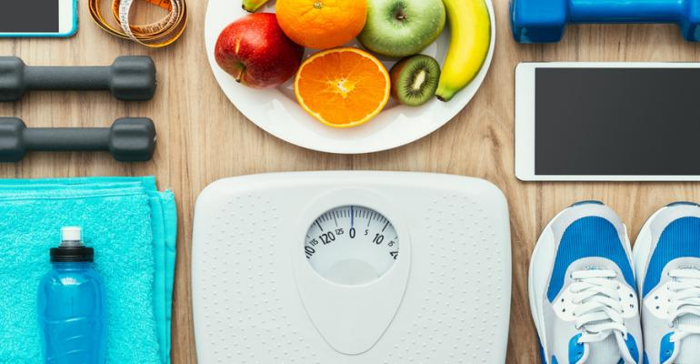 weight management concept with scales, fruit and workout equipment