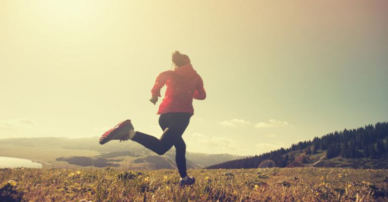 woman runs through countryside in late afternoon