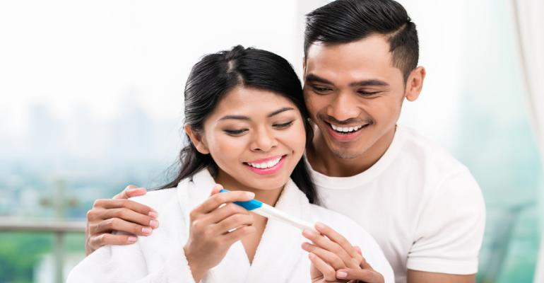 Woman and man looking happy with pregnancy test