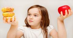 Girl chooses between apple and doughnuts